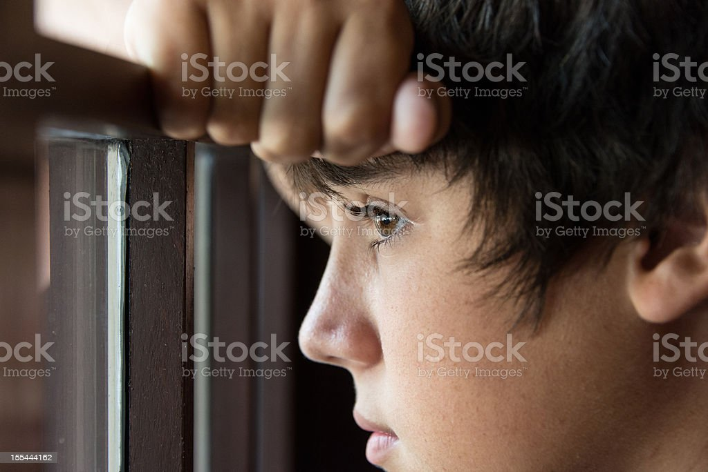 Pensive teenager looking through a window stock photo