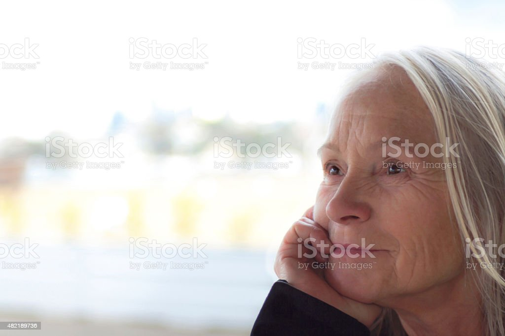 Pensive, thinking blond senior woman with brown eyes, copy space stock photo