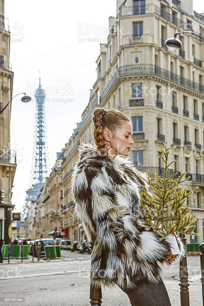 pensive trendy fashion-monger with Christmas tree in Paris stock photo