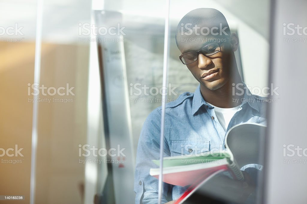 Pensive university student reading book in window royalty-free stock photo