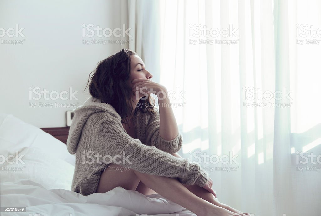 Pensive woman in bed stock photo