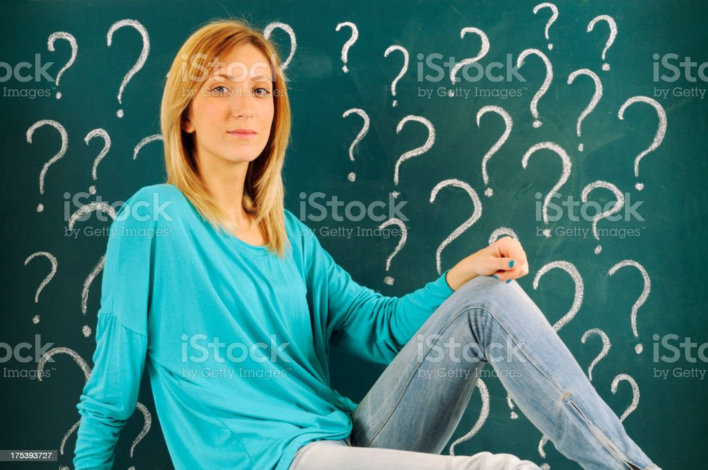 Pensive Woman in front of Question Marks Sketched on Blackboard royalty-free stock photo
