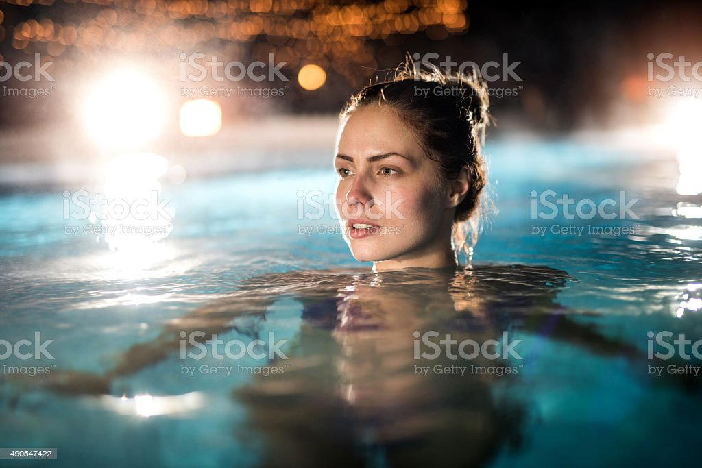 Pensive woman in the heated swimming pool outdoors. stock photo