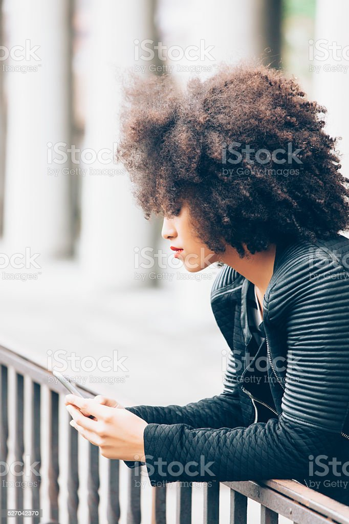 Pensive woman looking at the phone and laening on fence stock photo