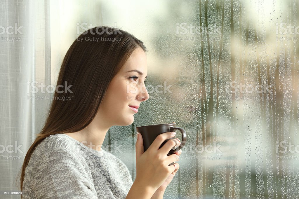 Pensive woman looking through a window stock photo
