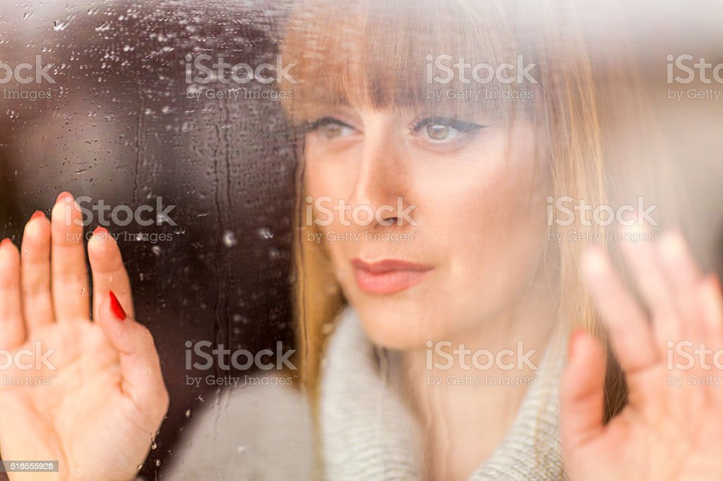 Pensive woman looking through window on rainy day stock photo
