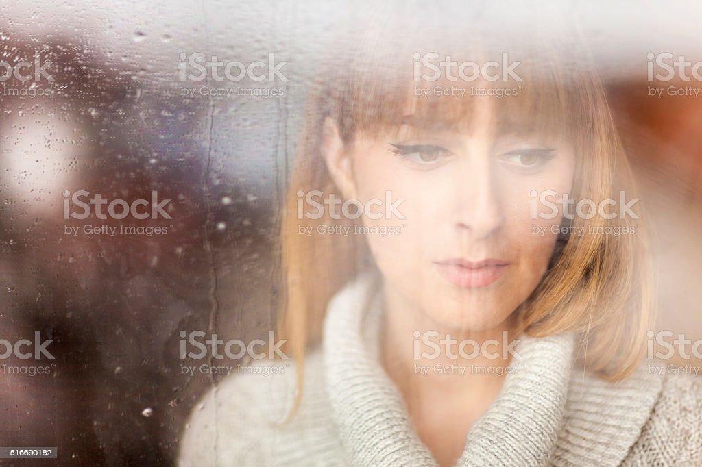 Pensive woman looking through window on rainy day stock photo