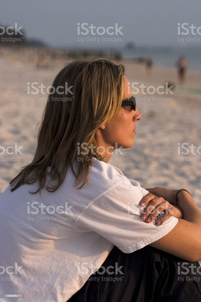 Pensive Woman On The Beach At Sunset stock photo