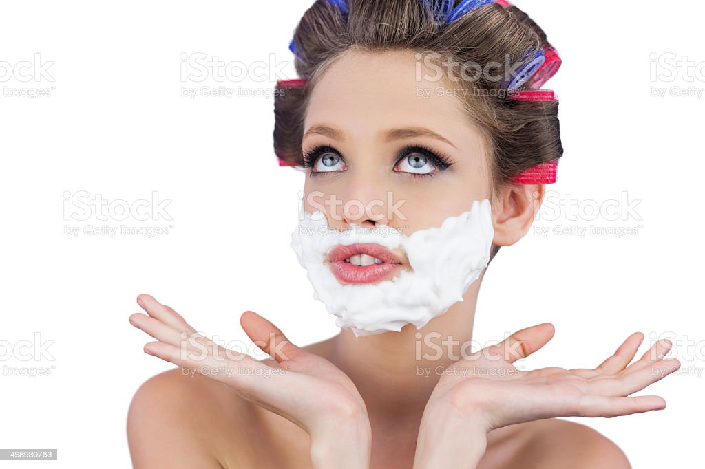 Pensive woman posing with shaving foam on face stock photo
