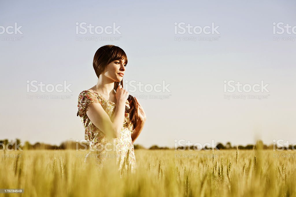 Pensive woman walking in a field royalty-free stock photo