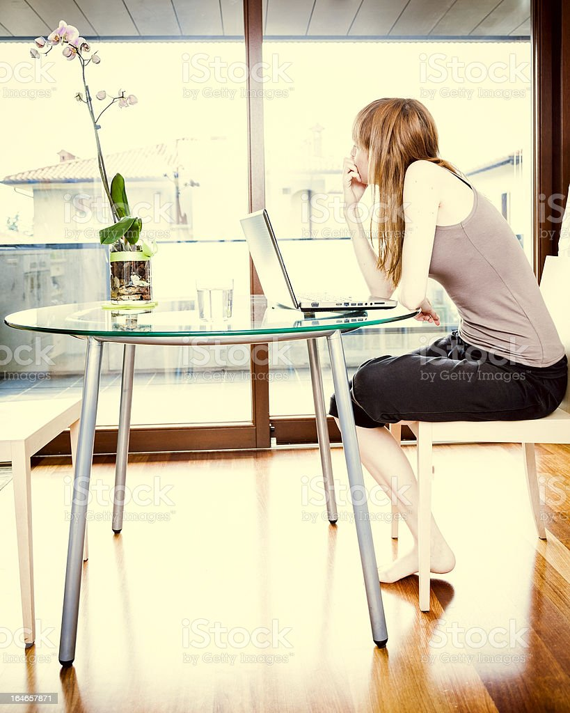 Pensive Woman With Laptop at Home stock photo