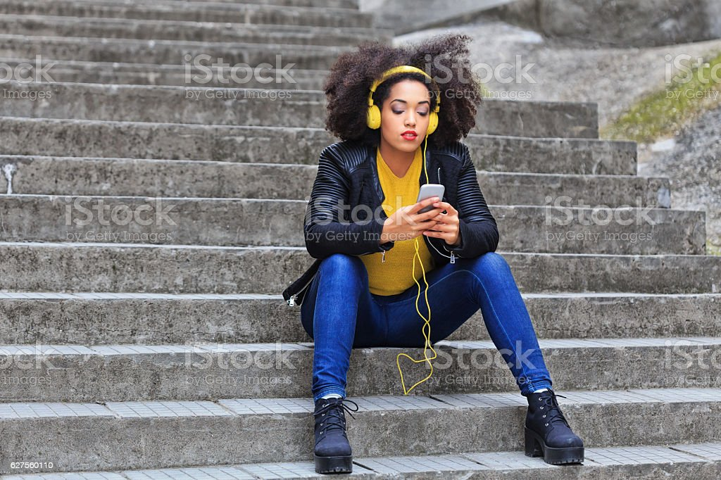 Pensive woman with yellow headphones listening music on stairs stock photo
