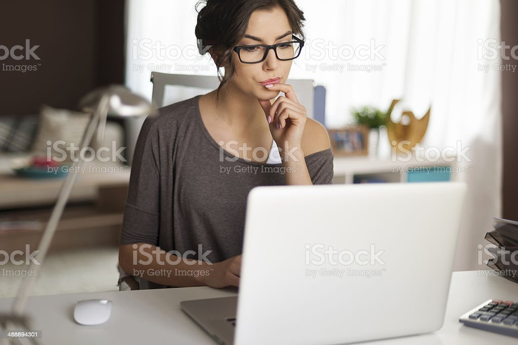 Pensive woman working at home stock photo