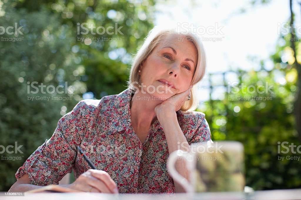 Pensive woman writing in journal at patio table royalty-free stock photo