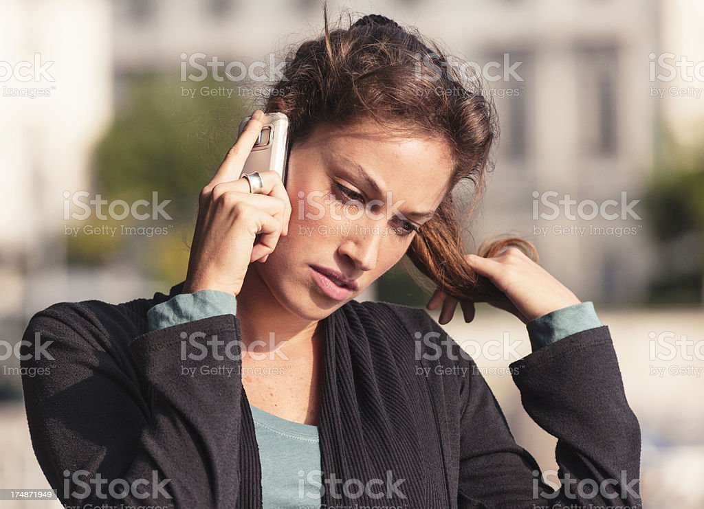 Pensive young adult on the phone royalty-free stock photo