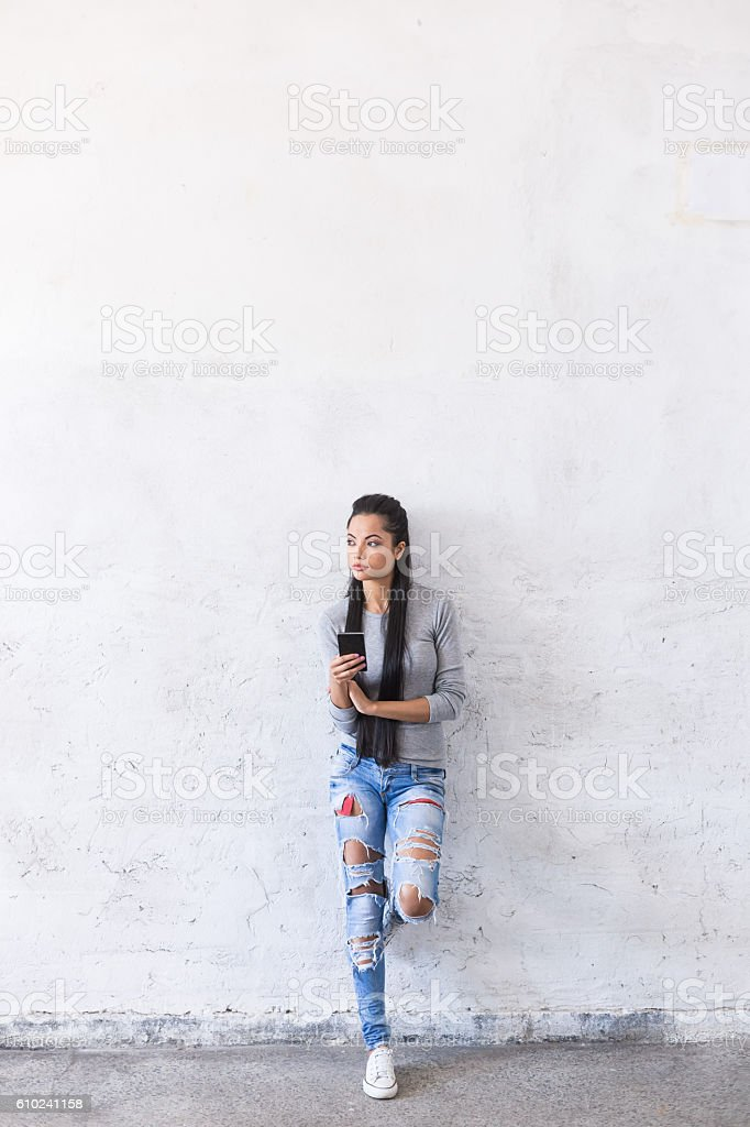 Pensive young asian woman leaning back on blank wall stock photo