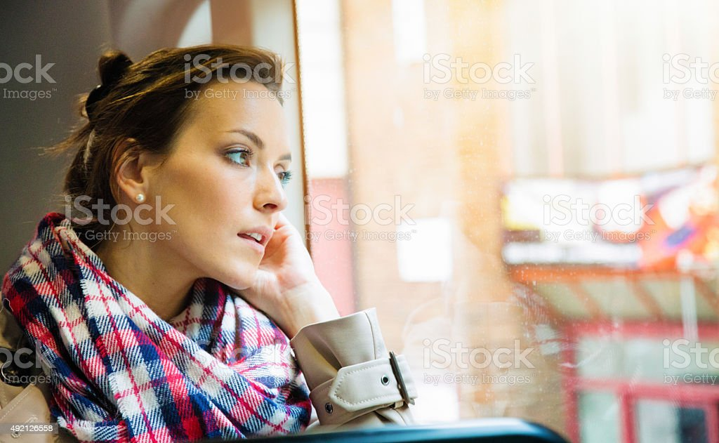 Pensive young British woman looking out of London bus window stock photo