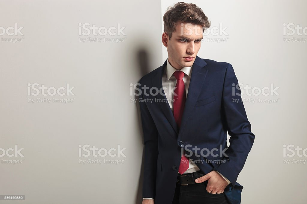 Pensive young business man looking down stock photo