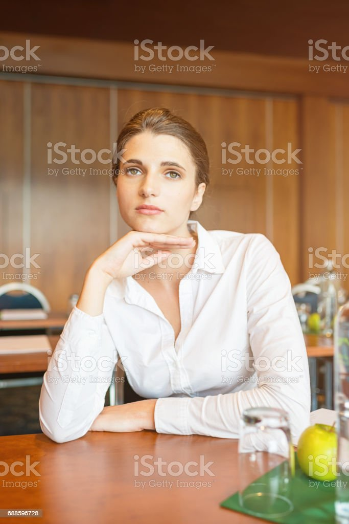 Pensive Young Businesswoman in Business Seminar stock photo