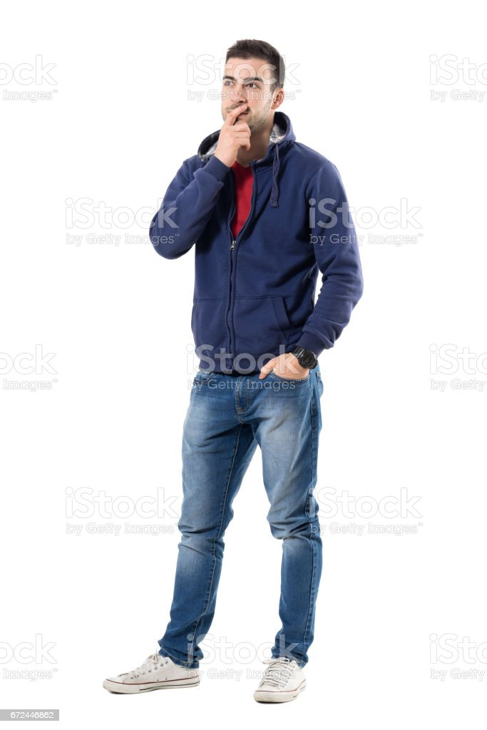 Pensive young casual guy with hand on chin looking up interested stock photo