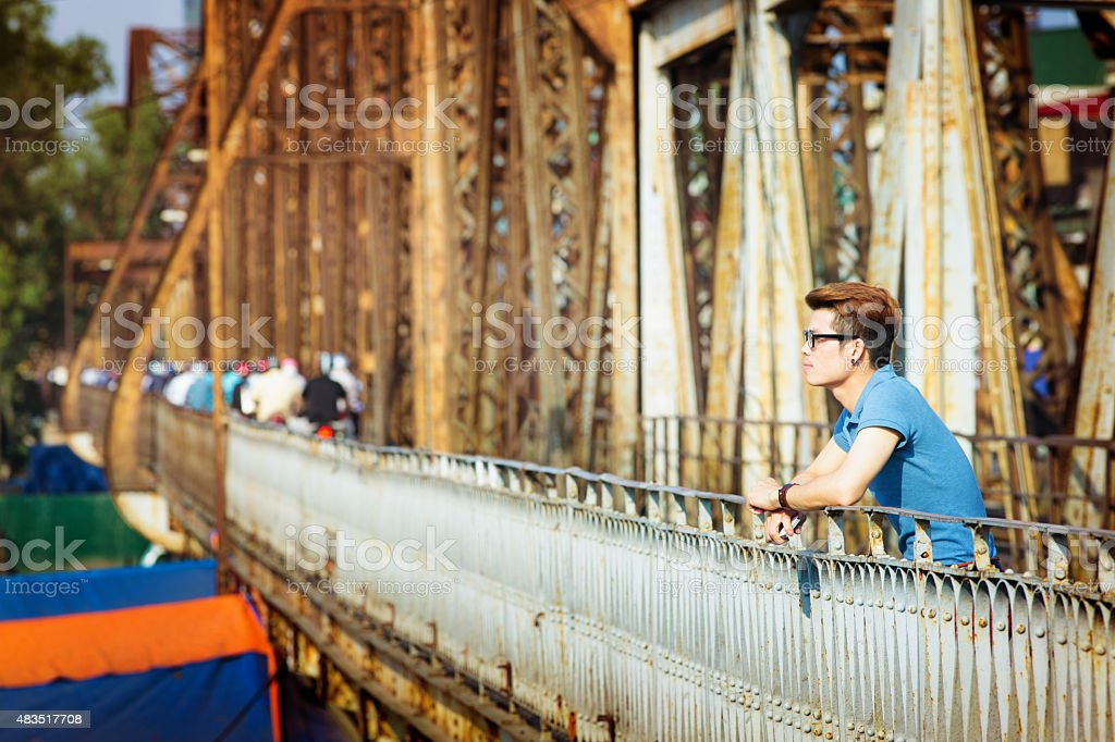 Pensive young man relaxes  on Long Bien Bridge Hanoi Vietnam stock photo