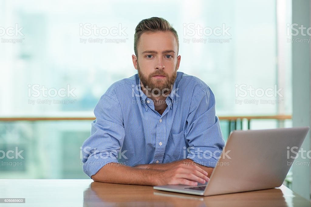 Pensive Young Man Working on Laptop at Cafe Table stock photo