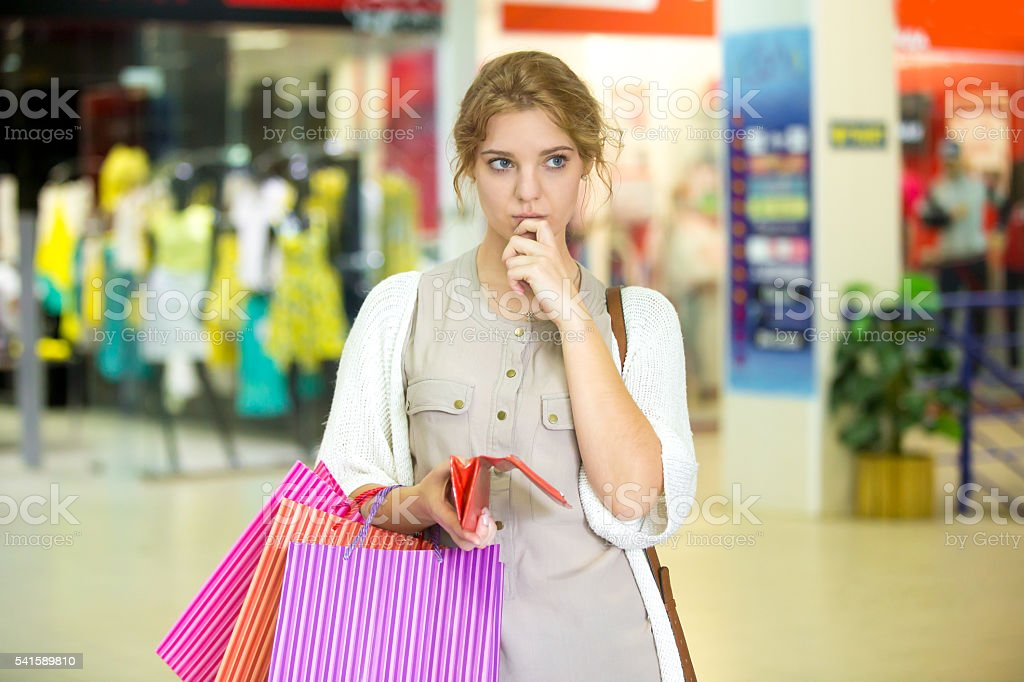 Pensive young woman holding empty wallet after shopping stock photo