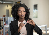 Pensive young woman in modern office holding pen