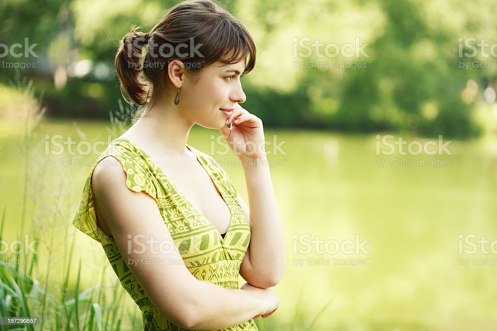 Pensive Young Woman Looking at Pond Outside royalty-free stock photo