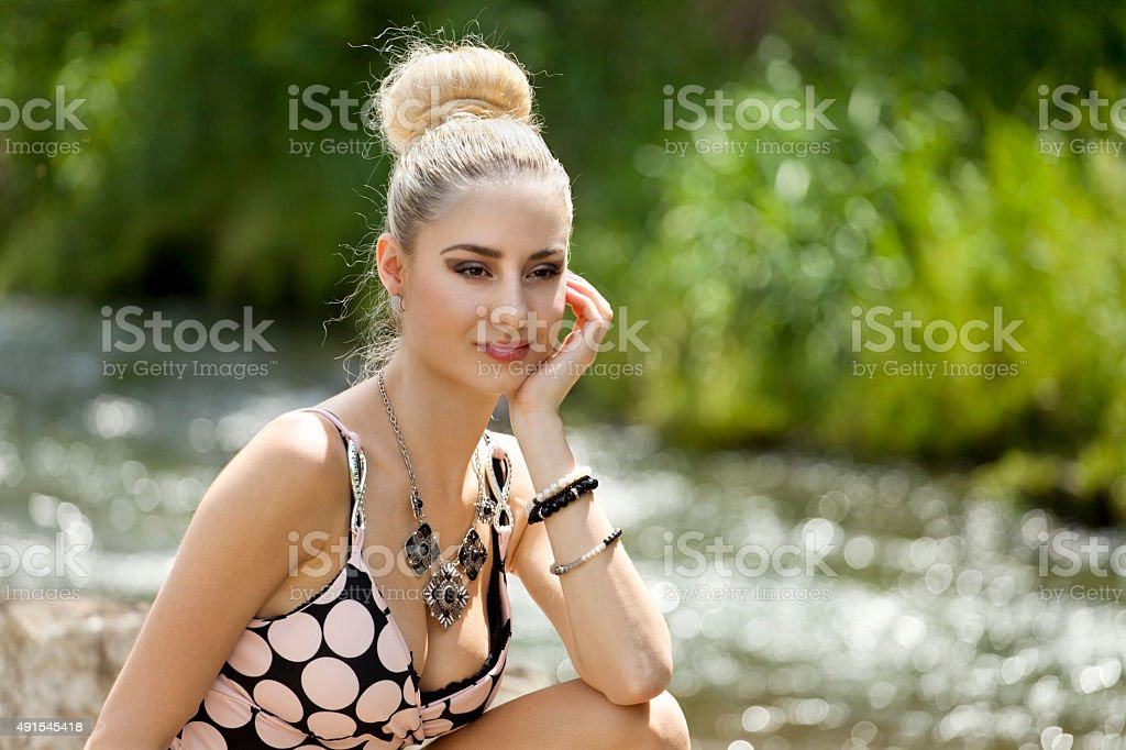 Pensive young woman on rock by river stock photo