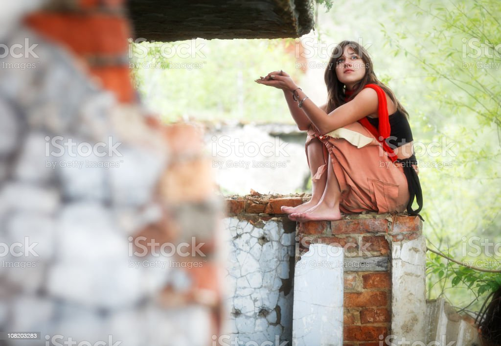 Pensive Young Woman Sitting on Brick Wall royalty-free stock photo