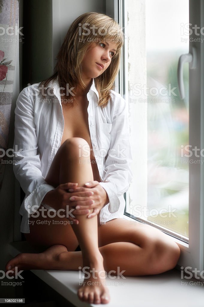 Pensive Young Woman Sitting on Window Sill stock photo