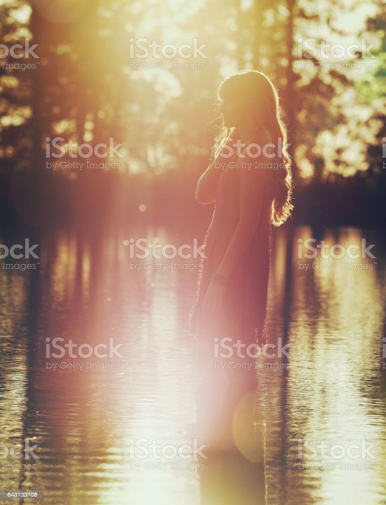 Pensive Young Woman Wading in Lake at Sunset stock photo