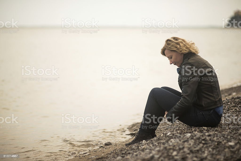 Pensive/dreaming woman on the beach stock photo