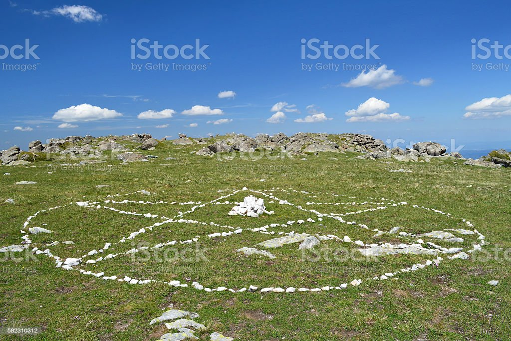 Pentagram drawn by white stones on the green grass stock photo