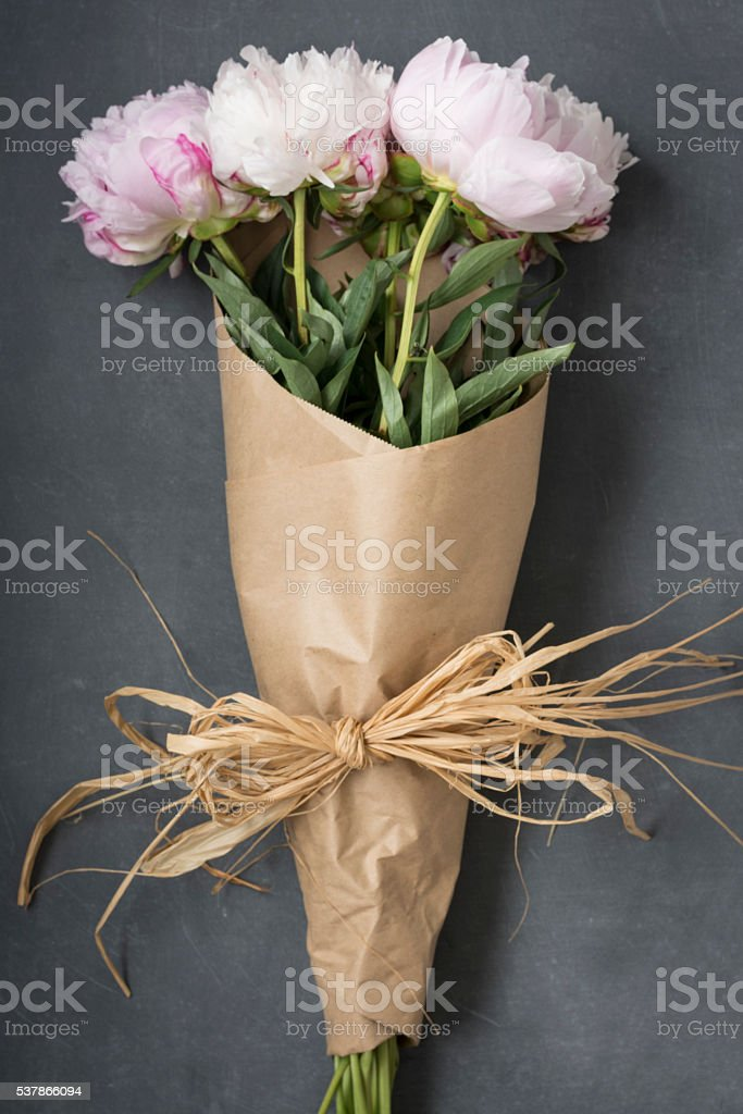 Peonies wrapped in floral paper stock photo
