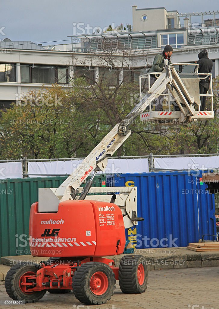 peope on lift platform are checking electric cable outdoor stock photo