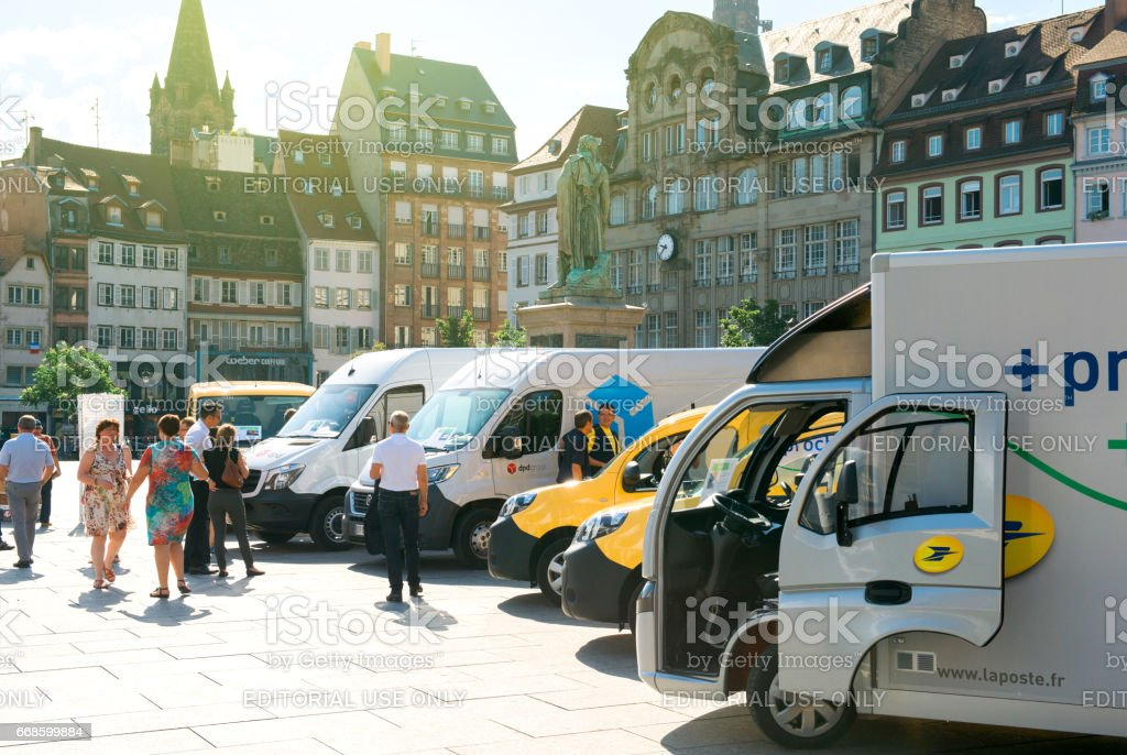 People admiring the fleet of electrical vehicles of postal operator La Poste stock photo