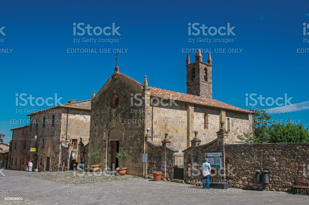 People and church at the hamlet of Monteriggioni stock photo