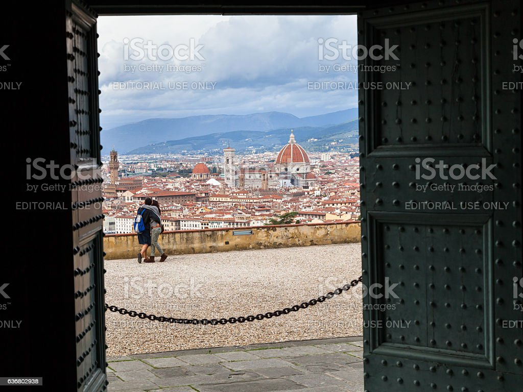 people and Florence city through doors of Basilica stock photo