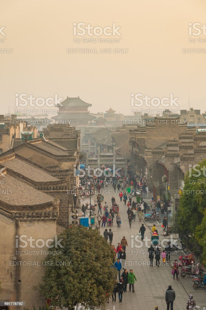 people and shops on walk street in evening at XiangYang city wall. stock photo