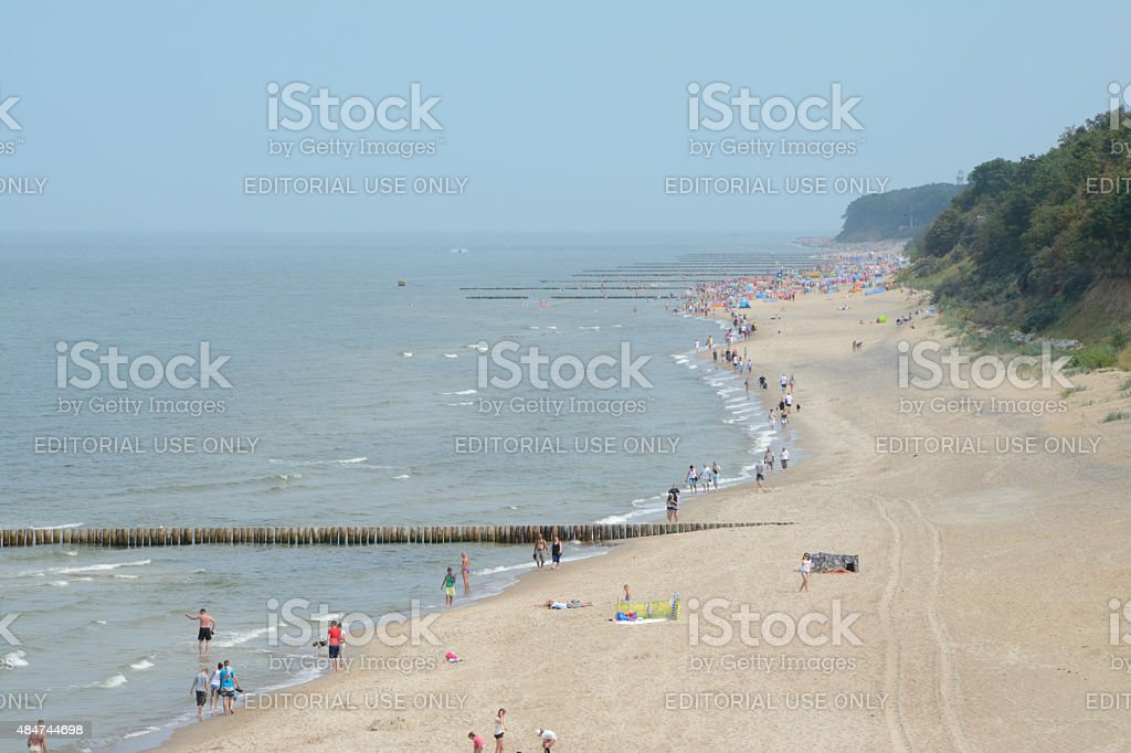 People and wooden groynes on Beach. stock photo