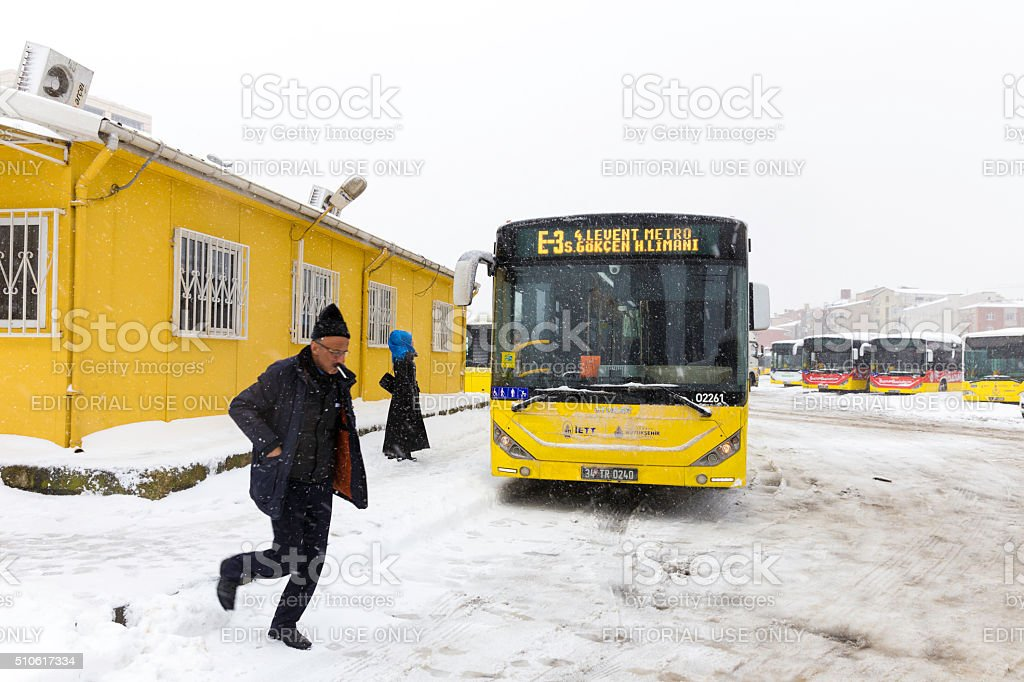People and yellow public bus on a snowy winter day stock photo