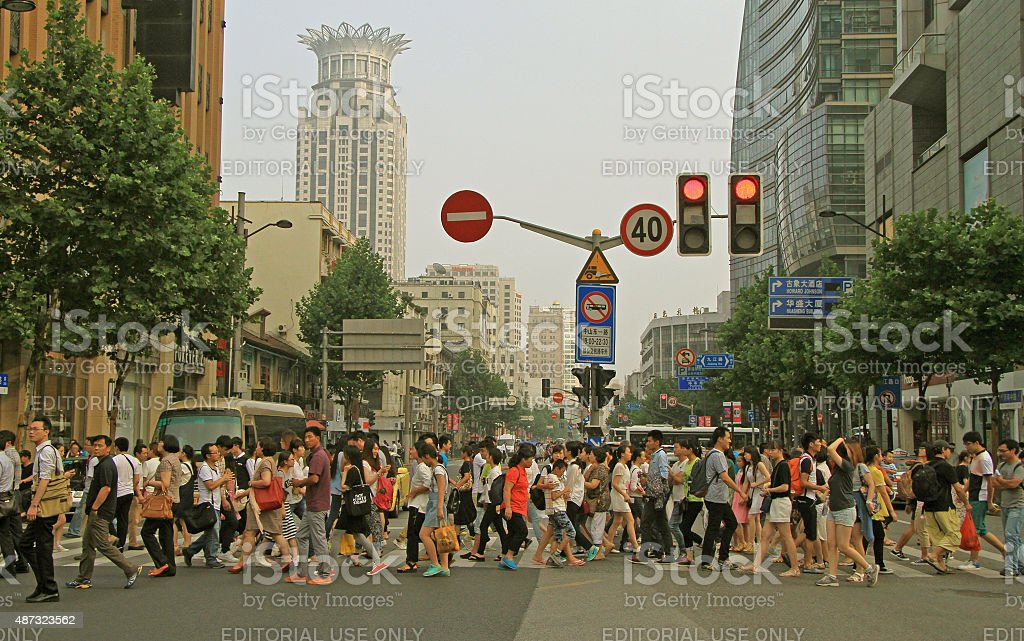 people are crossing road by crosswalk in Shanghai, China stock photo