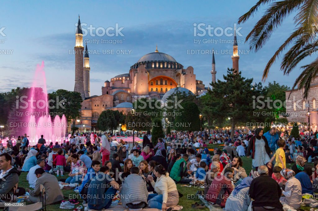 People are eating iftar(evening meal,dinner) during Ramadan in Hagia sophia square. Hagia sophia district is the most popular place for Ramadan activities in Istanbul stock photo