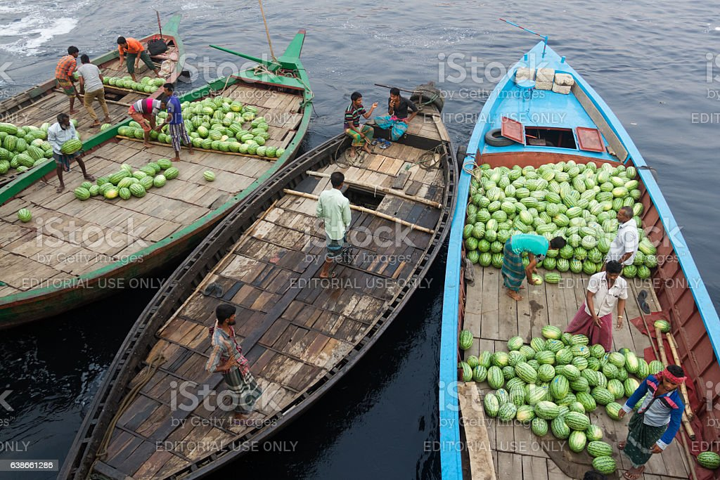 People are loading watermelons to small boat from ferry. stock photo