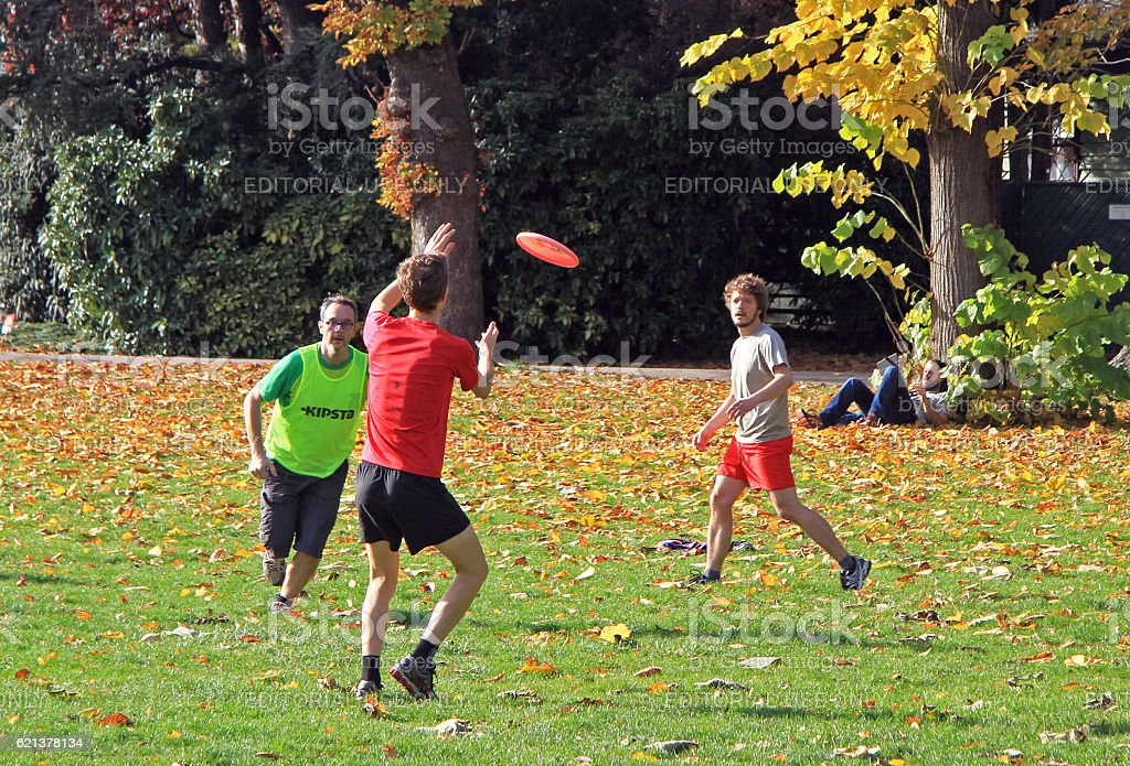 people are playing frisbee in city park stock photo