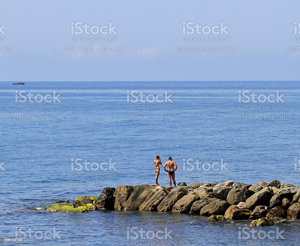 people are resting on a stone pier in Khosta, Russia stock photo