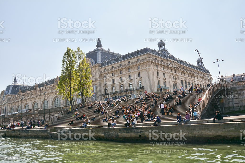 People are siting on the stairs of the louvre waterfront stock photo