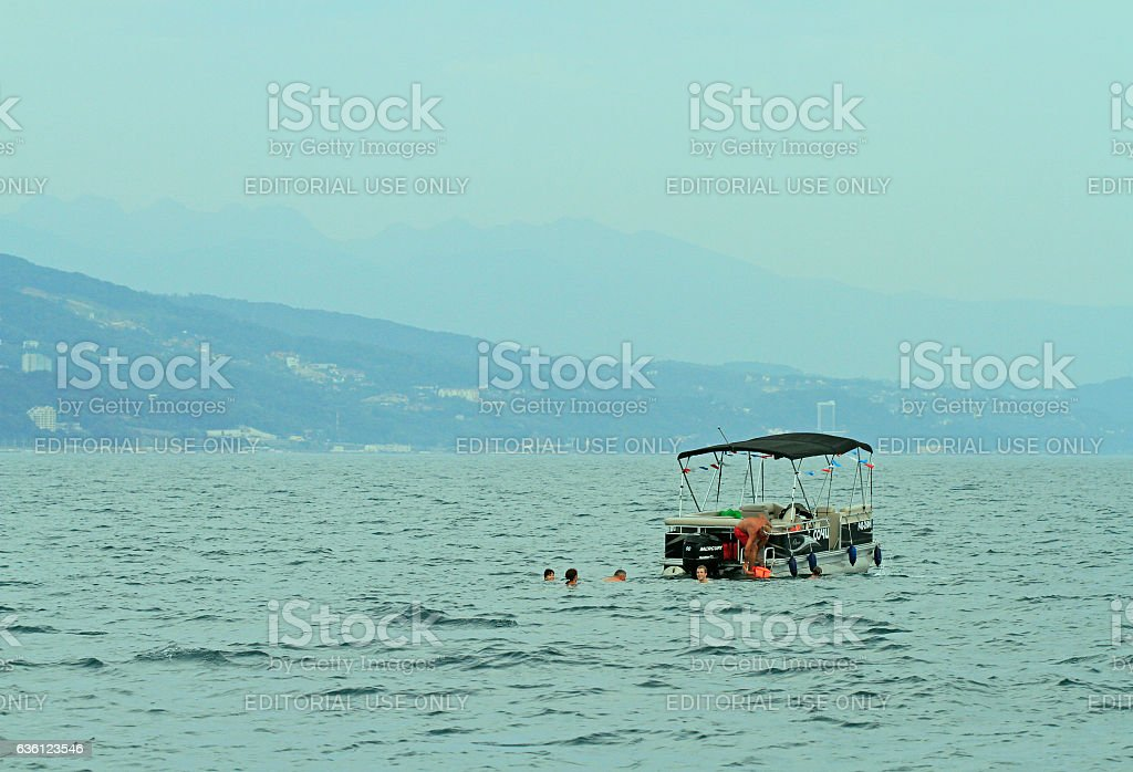 people are swimming in the open sea stock photo